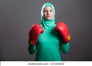 Serious boxing athlete muslim woman in green hijab or islamic sport wear standing, with boxing gloves and looking at camera with serious face. indoor studio shot, isolated on dark grey background
