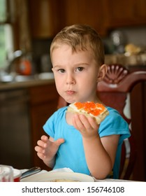 Serious boy eating red caviar