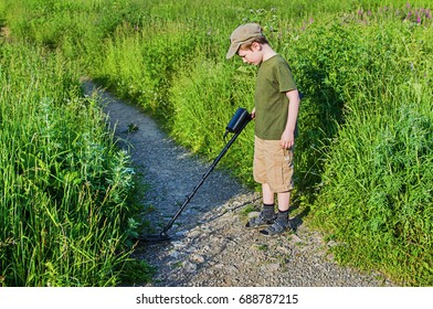 serious boy with a metal detector examines the soil on a rocky trail on a summer evening