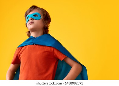Serious boy in superhero costume keeping hands on waist and looking away while standing against bright yellow background