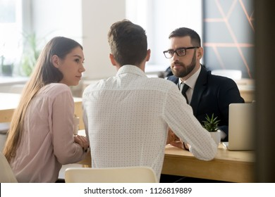 Serious broker or realtor listening to millennial couple arguments or ideas during office meeting, insurance agent consulting clients on house purchase, becoming property owners or taking loan.