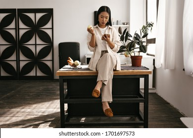 Serious brunette Asian woman in beige pants and cardigan sits on wooden table on kitchen. Charming lady eats fresh apple and holds phone.