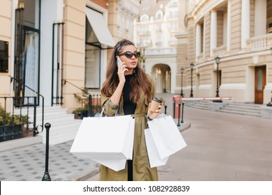 Serious brunette fashionista lady talking on phone during shopping in autumn weekend. Good-looking shopaholic woman spending time outdoor and making purchases.