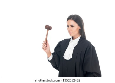 Serious brunette judge in judicial robe holding gavel isolated on white