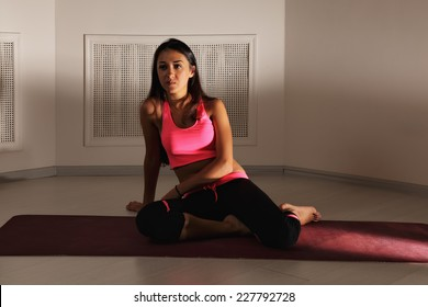 Serious brunette woman in dark gym sitting on a red mat