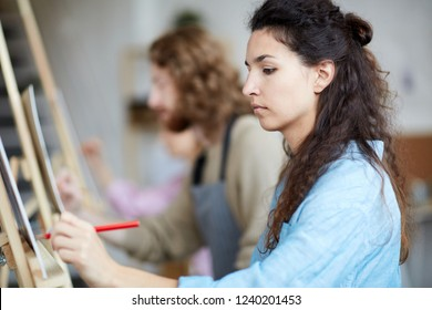 Serious brunette woman sketching with pencil at lesson of painting in school of arts