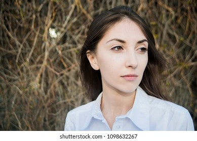 serious brunette young womam wear white shirt and stand against fencr made from dry grass or bush. asian girl