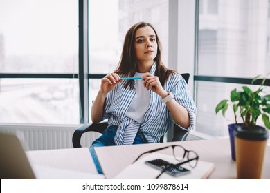 Serious brunette young woman sitting at desktop looking away pondering on idea for working project, creative female designer puzzled on business spending time at loft interior office holding pen