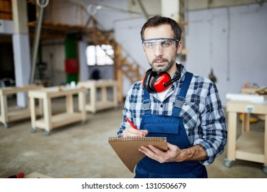 Serious brutal bearded carpenter in protective goggles wearing ear protectors on neck making notes in sketchpad and looking at camera while standing in workshop