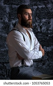 Serious and brutal businessman in thinking process. Dark hair and beard wearing jacket. Against the wall.