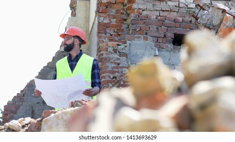 Serious builder analysing drawing. Bearded building engineer in helmet on destroyed building background. Ruins and stones in the foreground