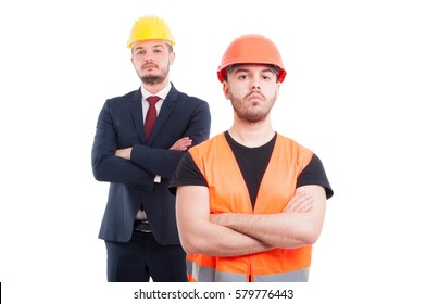 Serious builder and architect behind him standing with arms crossed on white background