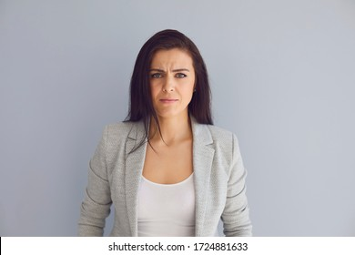 Serious business lady looking at camera on gray background