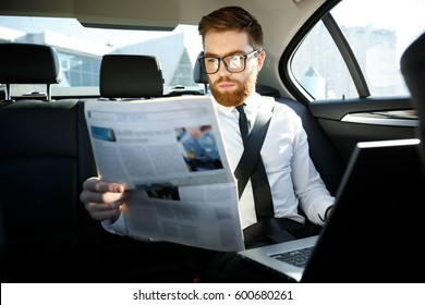 Serious business man in shirt and eyeglasses sitting on back seat of a car with laptop while reading a newspaper