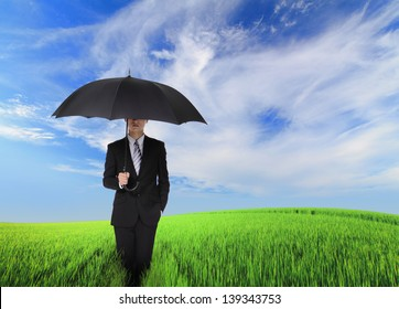 serious business man standing oh the green field and holding black umbrella, concept for business