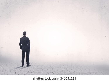 Serious business man standing on grey brick floor and thinging about decisions concept