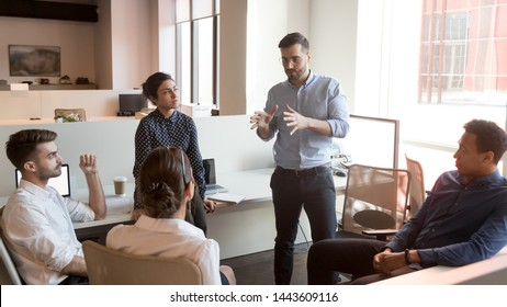 Serious business man team leader coach mentor talk to diverse business people in office explain strategy at corporate group meeting, multiethnic staff listen to boss instruct interns at briefing