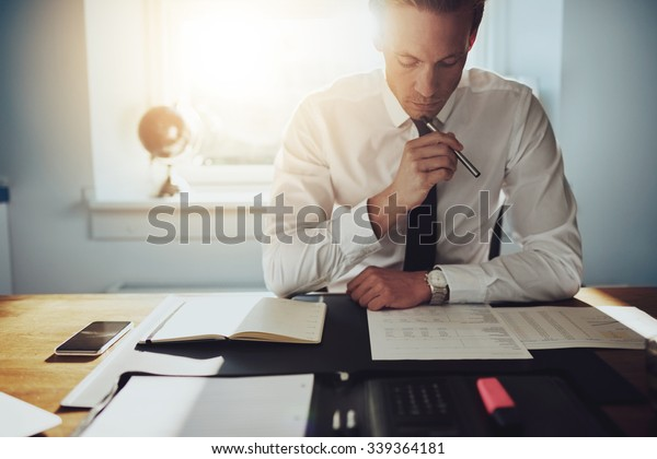 Serious business man working on documents looking concentrated with briefcase and phone on the table