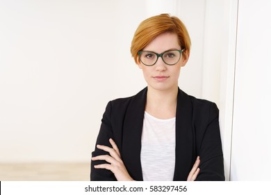 Serious business manageress wearing glasses staring intently at the camera with crossed arms as she stands in the office, with copy space
