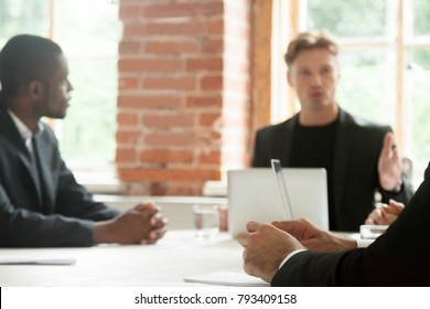 Serious business negotiators talking during stressful negotiations, focus on hands of businessman in tension making important decision, feeling pressure stress or being scolded by boss at meeting