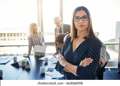 Serious business woman in front of team, looking at camera