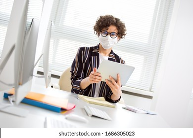 A serious business woman in medical mask working alone in an empty office