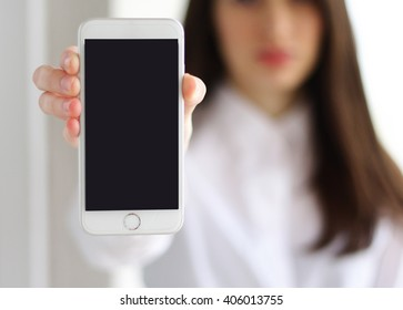 serious business woman showing blank smartphone screen over  background. mock up iphone 6, mockup iphone screen, Focus on smartphone. iPhone 6s modern  mock up concept