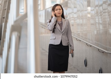 Serious business woman talking on mobile phone with client while walking in the city