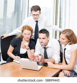 Serious business workers looking at laptop computer while their boss explaining to them new business strategy that will be represented in the company.