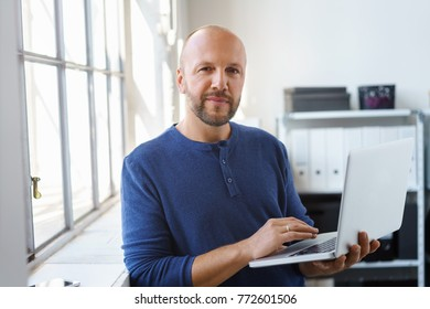 Serious businessman in a casual shirt standing leaning against a bright window sill holding a large binder