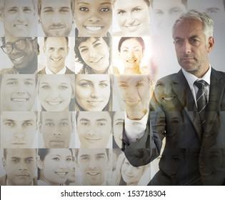 Serious businessman choosing future employees on digital interfaces