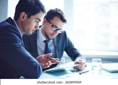 Serious businessman explaining data to his colleague at meeting