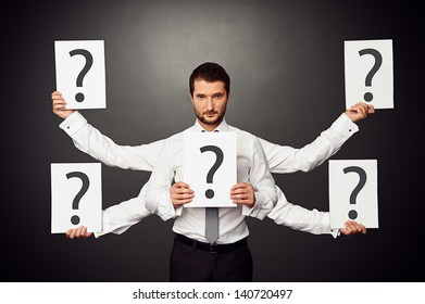 serious businessman with five hands holding placards with question marks