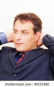 Serious businessman in formal wear with hands behind head