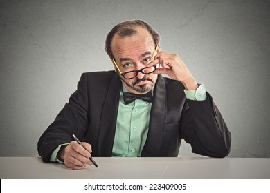 Serious businessman with glasses skeptically looking at you sitting at his desk isolated on office grey wall background. Human face expression, body language, attitude