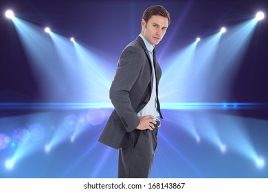 Serious businessman with hands on hips against cool nightlife lights