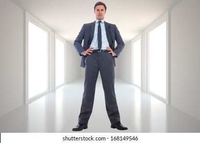 Serious businessman with hands on hips against digitally generated room