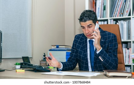 Serious businessman having a discussion by phone sitting in the office