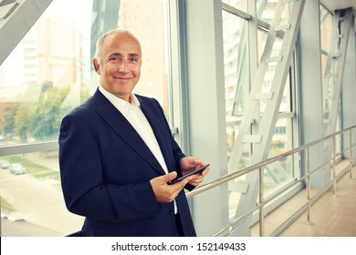 serious businessman holding tablet pc and looking at camera