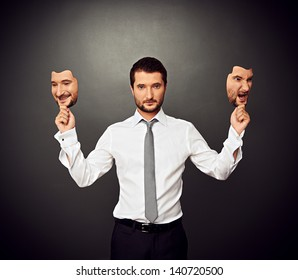 serious businessman holding two masks with different mood