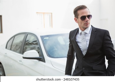 Serious businessman leaning against his car in a car park