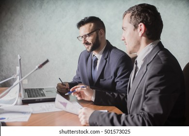 Serious businessman listening to his colleague explanations at meeting