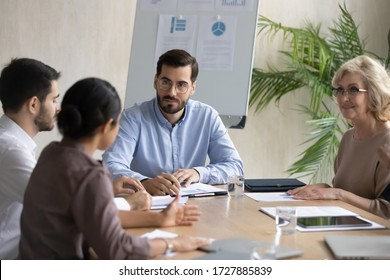 Serious businessman listening indian employee about project sit at table in boardroom at company meeting. Confident leader discuss business strategy with diverse woman and colleagues.