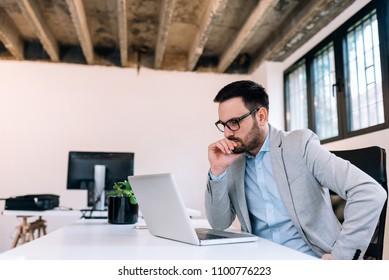 Serious businessman looking at laptop screen.
