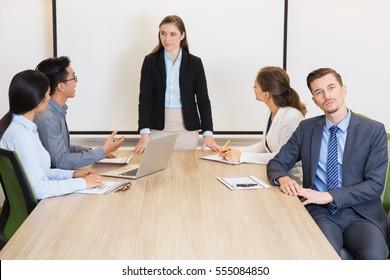 Serious businessman making presentation for team