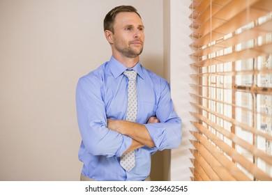 Serious businessman peeking through blinds in office