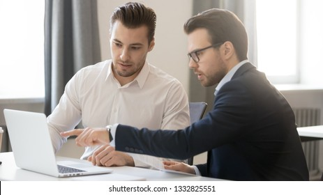 Serious businessman pointing at laptop discussing corporate software with colleague in office, executive male team working together use computer, manager mentor consulting instructing client coworker