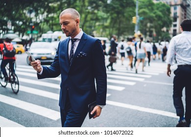Serious businessman read message on mobile phone after passing crowded crosswalk in megapolis city, handsome male manager in suit walking in downtown by foot reading news via application on smartphone