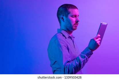 Serious businessman reading a handheld tablet computer in vibrant purple through blue lighting with rear copy space