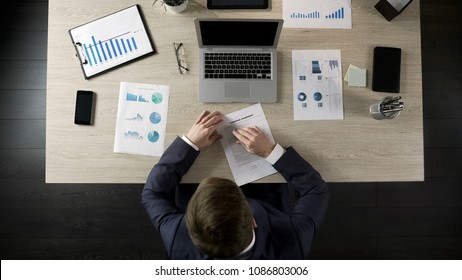 Serious businessman reading and signing purchase agreement, public procurement